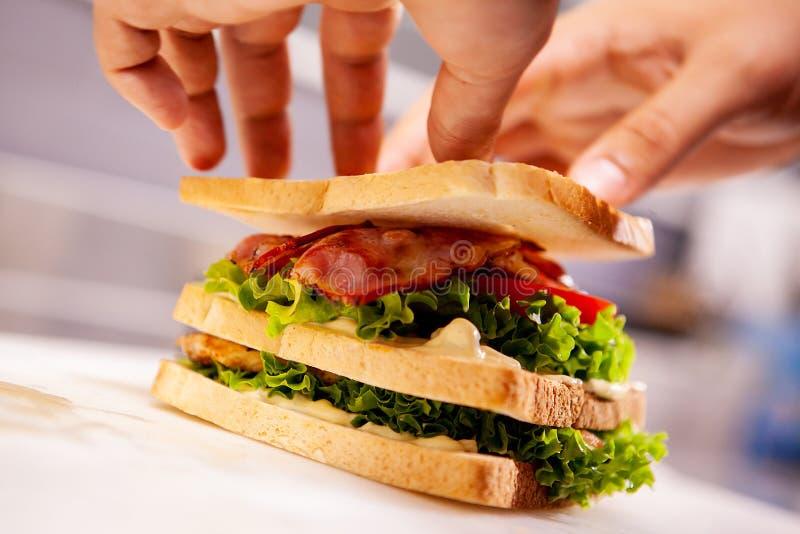 Chef, der Sandwich in der rustikalen Art mit Speck und Frischgemüse macht lizenzfreies stockbild