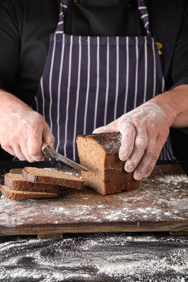 Chef in der schwarzen Uniform h?lt ein K?chenmesser in seiner Hand und schnitt St?cke Brot ab lizenzfreie stockfotos