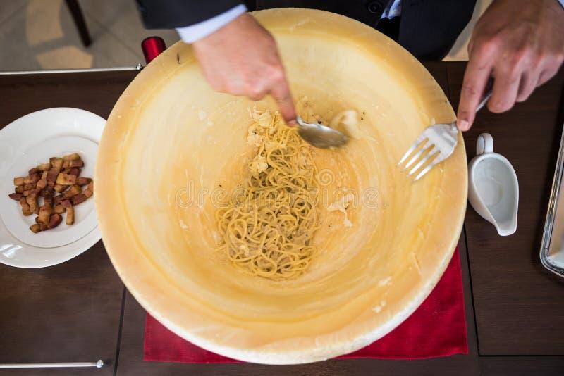 Chef, der Spaghettis carbonara im Käserad mit tourched Weinbrand und gebratenem Speck macht lizenzfreie stockfotografie