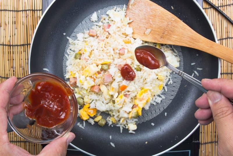Chef, der Tomatensauce für das Kochen des gebratenen Reises setzt lizenzfreie stockfotografie