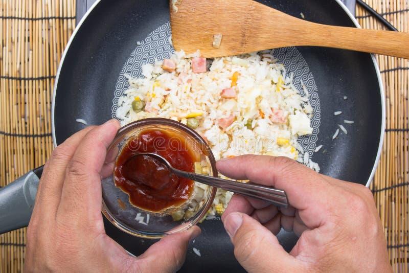 Chef, der Tomatensauce für das Kochen des gebratenen Reises setzt lizenzfreie stockbilder