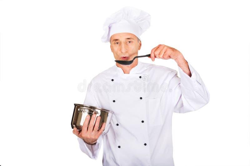 Chef in der weißen Uniform, die seine Suppe schmeckt lizenzfreie stockbilder