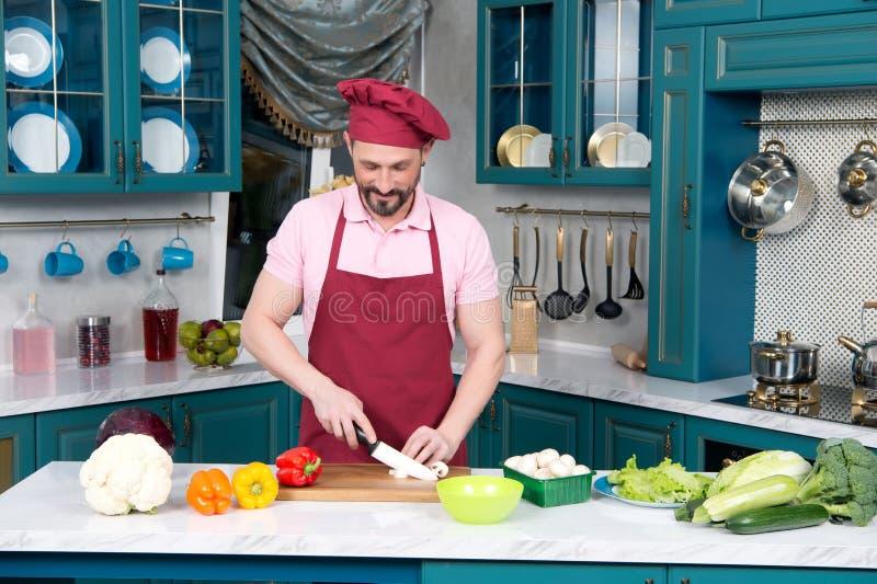 Chef des jungen Mannes schnitt Pilze auf der Küche stockfotos