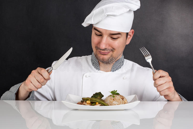 Chef eating his prepared food with cutlery. Black background royalty free stock photo