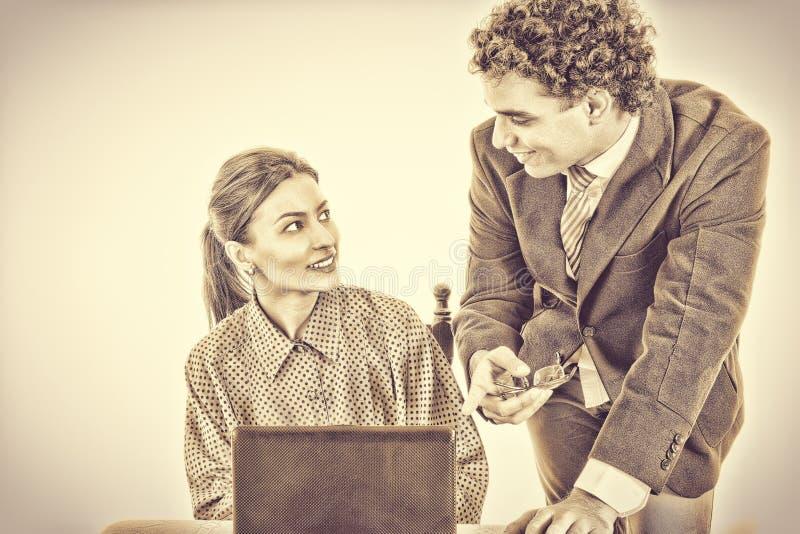 Chef- en glimlachende secretaresse die aan laptop samenwerken royalty-vrije stock afbeeldingen