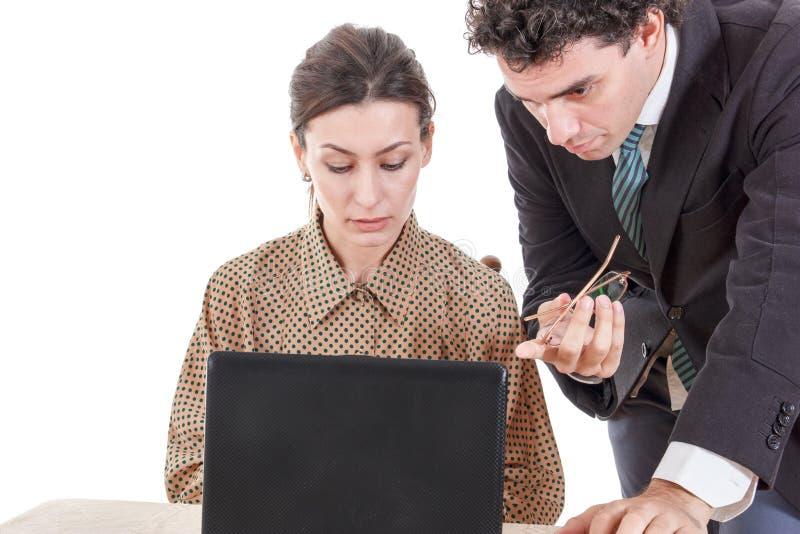 Chef- en ongerust gemaakte secretaresse die aan laptop samenwerken royalty-vrije stock afbeeldingen