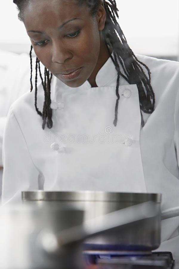 Chef féminin Cooking In Kitchen image stock
