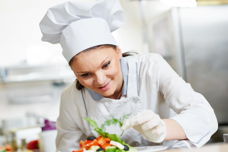 Chef féminin de cuisinier décorant la nourriture préparée de salade photographie stock libre de droits