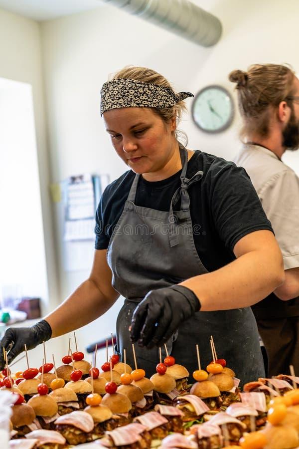 Chef féminin et masculin Putting Ingredients des hamburgers sur une diffusion découpée en tranches de pain sur un Tableau dans le image libre de droits