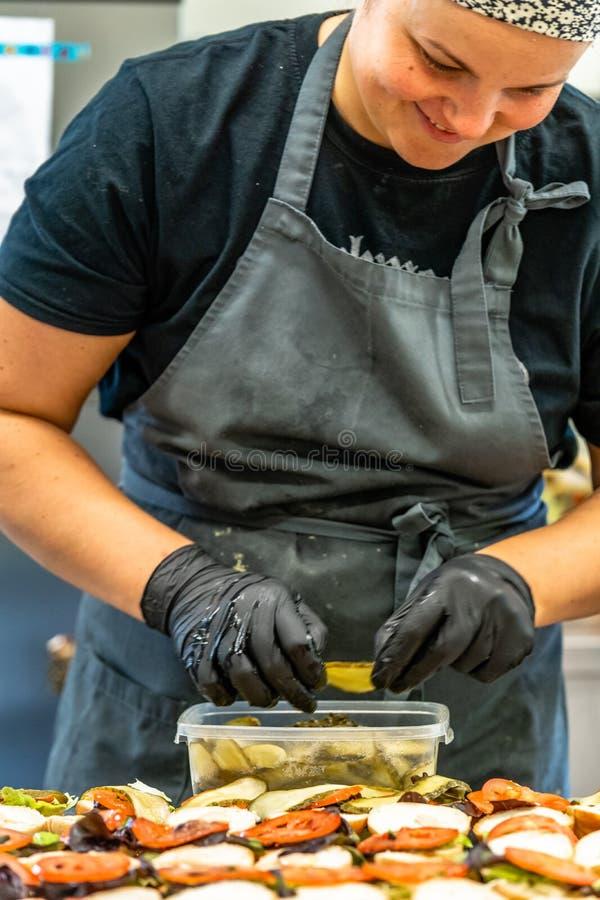 Chef féminin Putting Ingredients des hamburgers sur une diffusion découpée en tranches de pain sur un Tableau dans les gants noir photos stock
