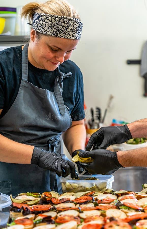 Chef féminin Putting Ingredients des hamburgers sur une diffusion découpée en tranches de pain sur un Tableau dans les gants noir photographie stock libre de droits
