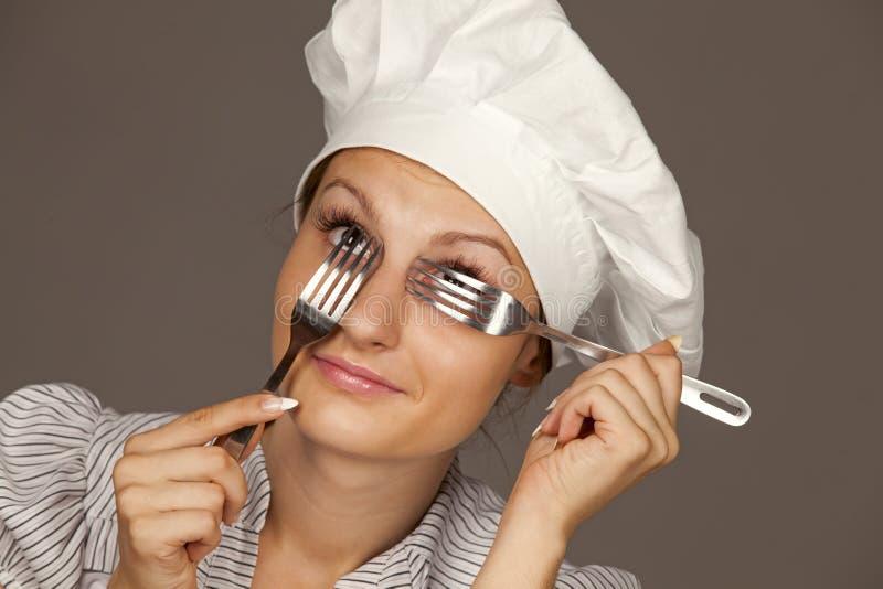 Chef féminin regardant par des fourchettes images libres de droits