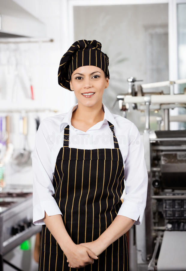 Chef féminin sûr Standing In Kitchen photo stock