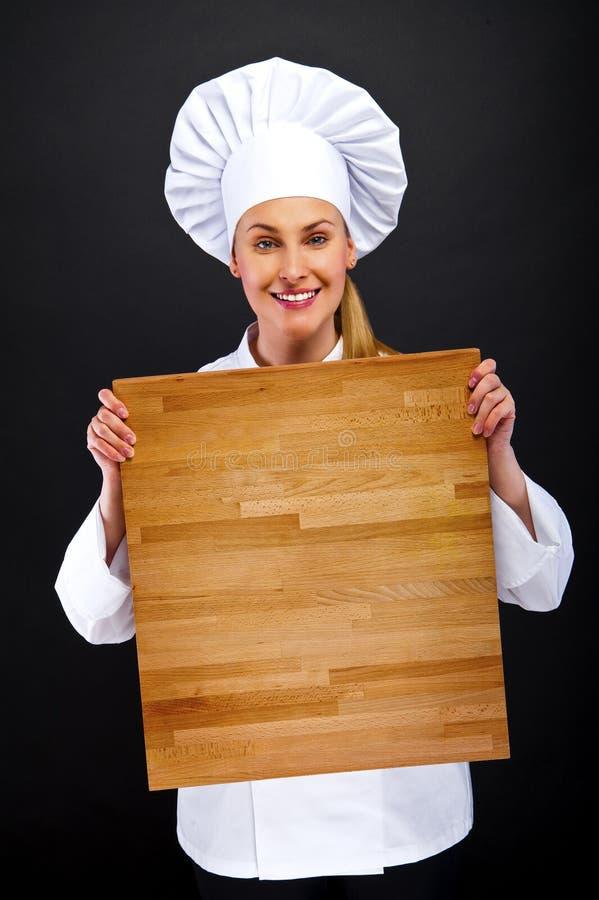 Chef féminin tenant les conseils en bois photo libre de droits
