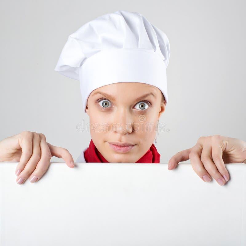 Chef féminin tenant une affiche pour le texte, le regard à l'affiche et le sourire image libre de droits