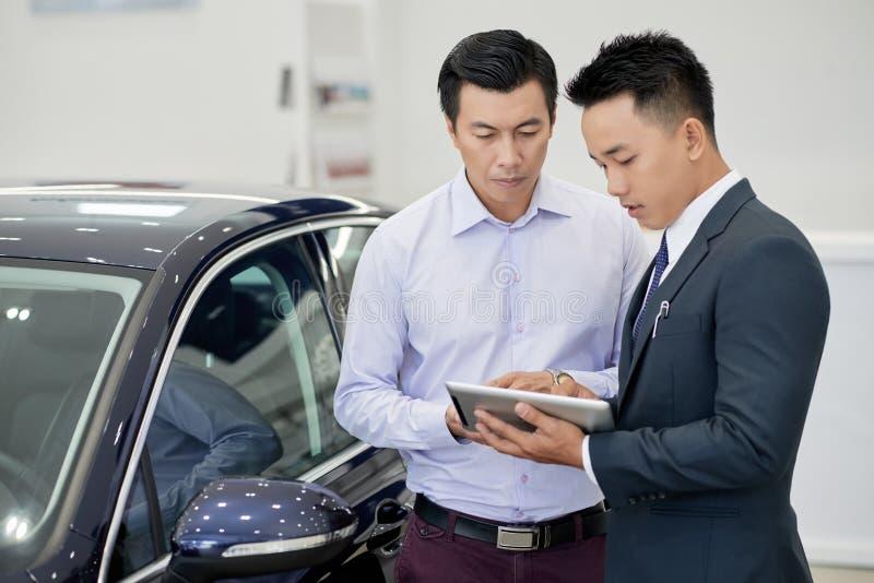 Chef för bilåterförsäljare som arbetar med klienten arkivfoto