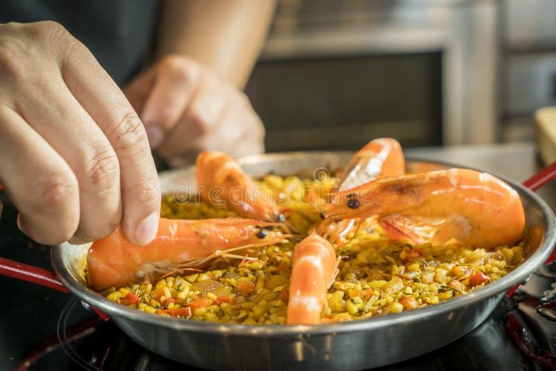 Chef fügt Meeresfrüchte Paella, Abschluss oben hinzu stockfoto