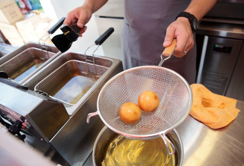 Chef faisant cuire la somme obscure dans une friteuse profonde images stock
