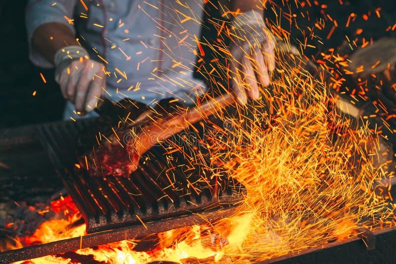 Chef faisant cuire le bifteck Le cuisinier tourne la viande sur le feu photos stock