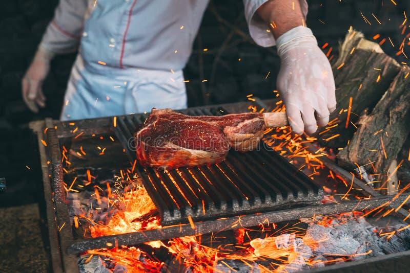 Chef faisant cuire le bifteck Le cuisinier tourne la viande sur le feu photos libres de droits