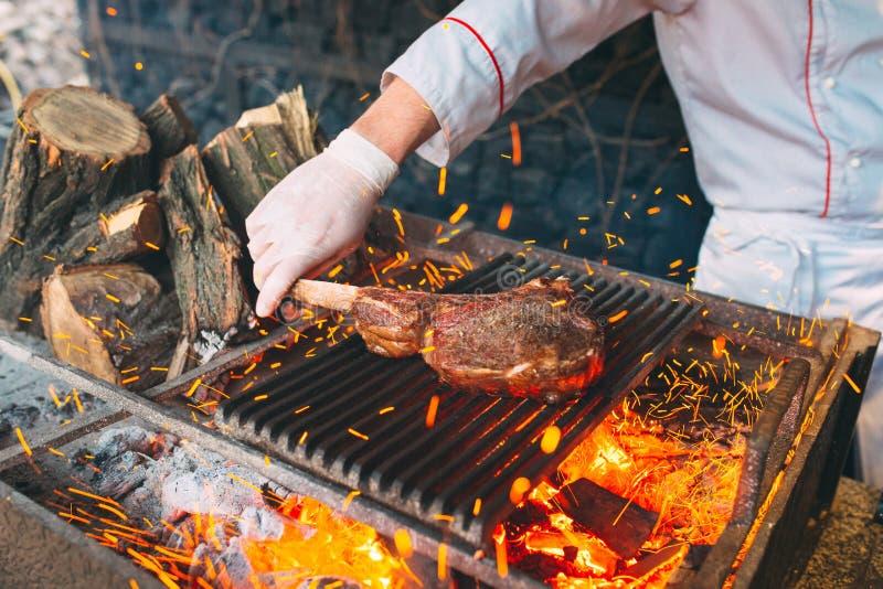 Chef faisant cuire le bifteck Le cuisinier tourne la viande sur le feu image stock