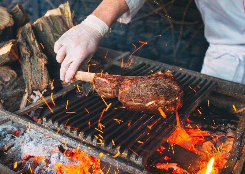 Chef faisant cuire le bifteck Le cuisinier tourne la viande sur le feu images stock