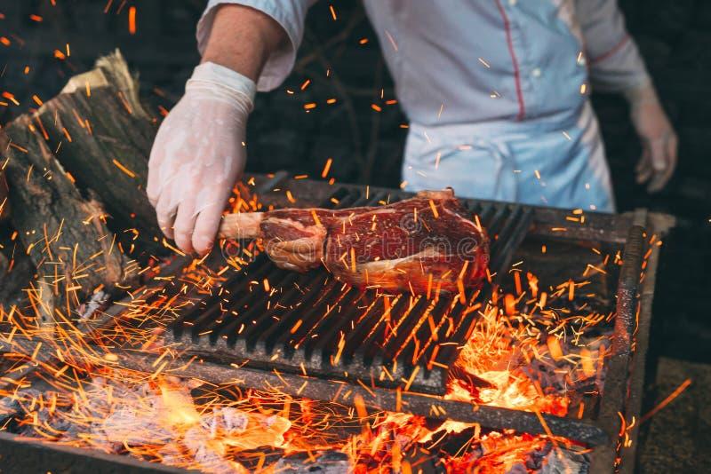 Chef faisant cuire le bifteck Le cuisinier tourne la viande sur le feu photo libre de droits