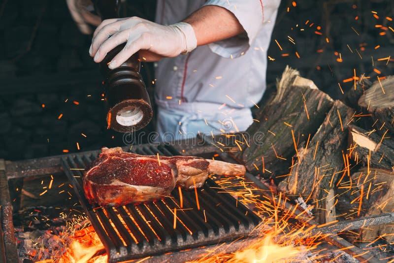Chef faisant cuire le bifteck Le cuisinier tourne la viande sur le feu images libres de droits