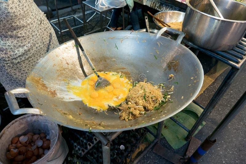 Chef faisant cuire les nouilles de riz faites sauter à feu vif thaïlandaises de protection avec la crevette photographie stock libre de droits