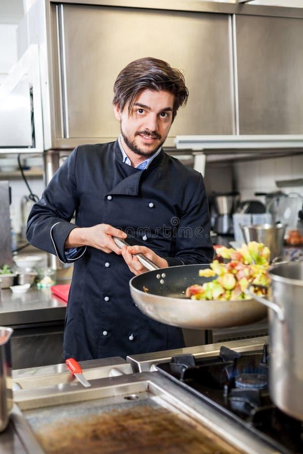 Chef faisant cuire un sauté de légumes au-dessus d'une fraise-mère photos libres de droits