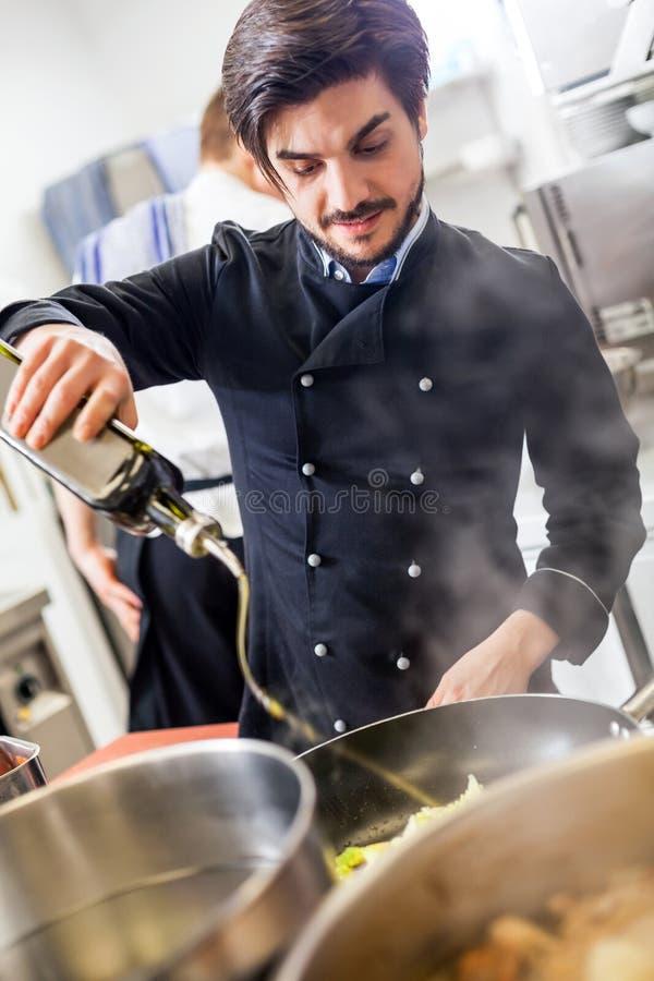 Chef faisant cuire un sauté de légumes au-dessus d'une fraise-mère photo stock