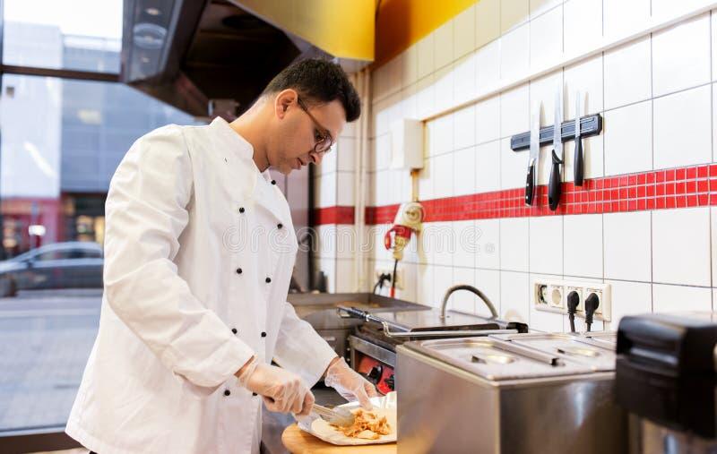 Chef faisant l'enveloppe de shawarma avec de la viande au chiche-kebab faire des emplettes image stock