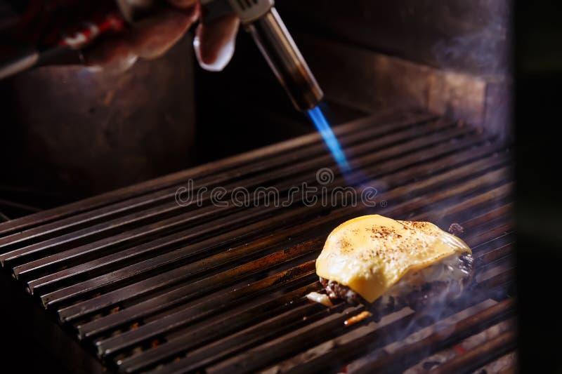 Chef faisant l'hamburger Le cuisinier fond le fromage sur un hamburger Le cuisinier emploie une lampe à souder pour fondre le fro image stock