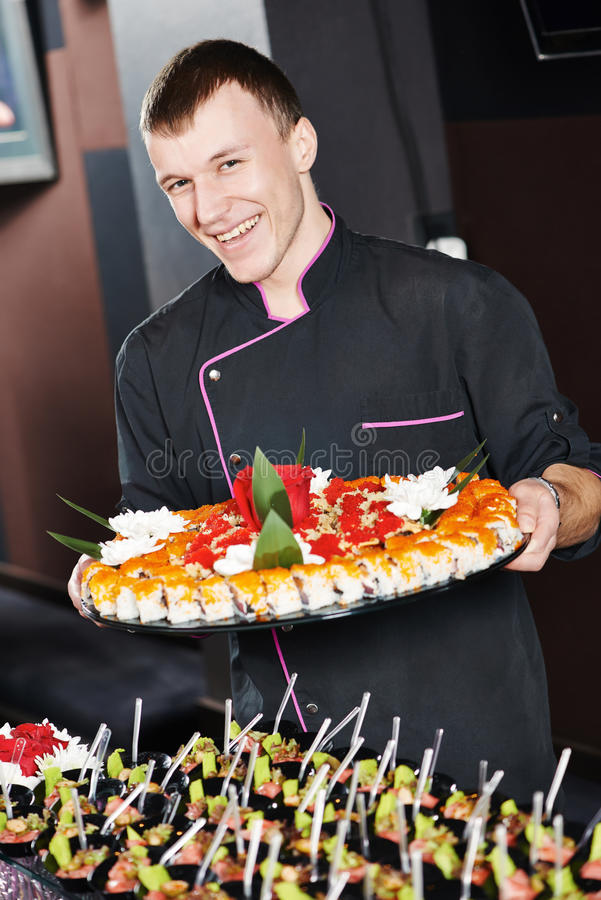 Chef with food on plates. Professional chef or waiter with sushi food dish on plates in restaurand cafe royalty free stock image