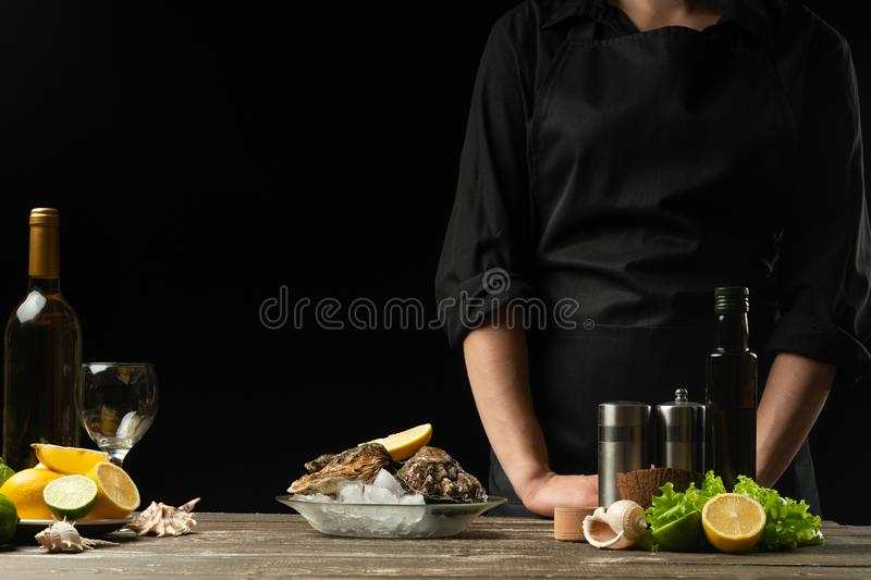 Chef with fresh oysters and a bottle of white dry wine on a dark background, horizontal photo, for seafood advertising stock photo