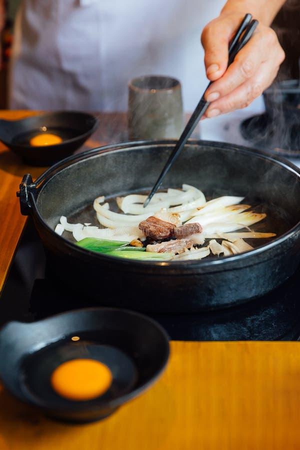 Chef fried onion, scallion and mushroom in Sukiyaki hot pot before adding Shoyu sauce soup for boiling Wagyu beef and Kurobuta. royalty free stock image