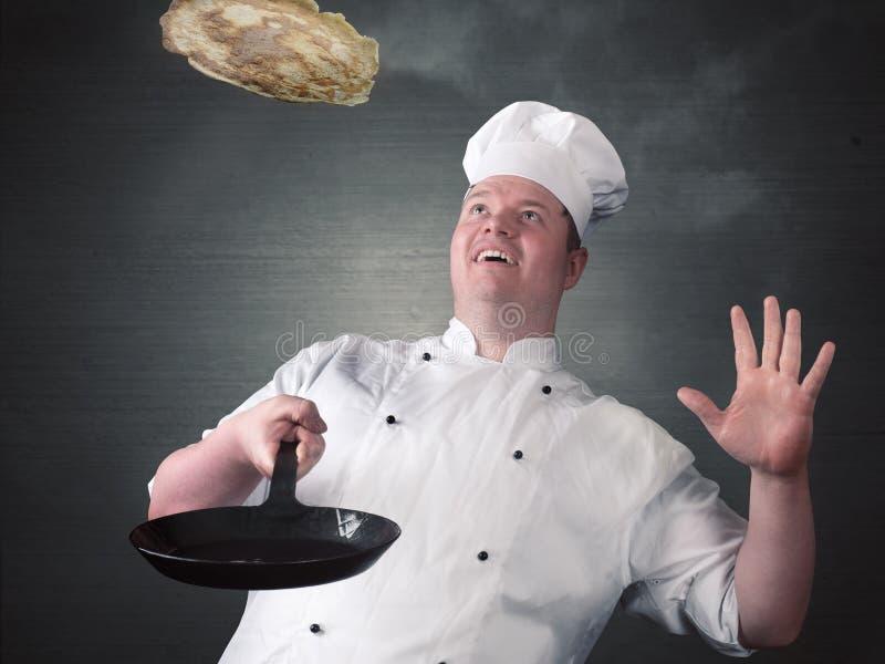 Chef fries fresh pancakes royalty free stock photo