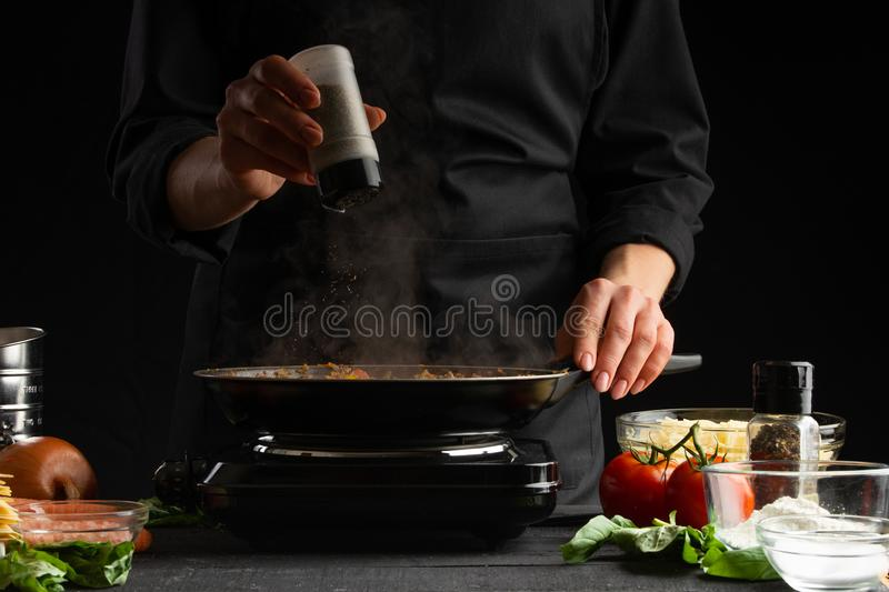Chef fries vegetables with meat for cooking a delicious dish. Peppers. Restaurant business and fast food. Gastronomy and cooking. Cooking lasagna royalty free stock photo