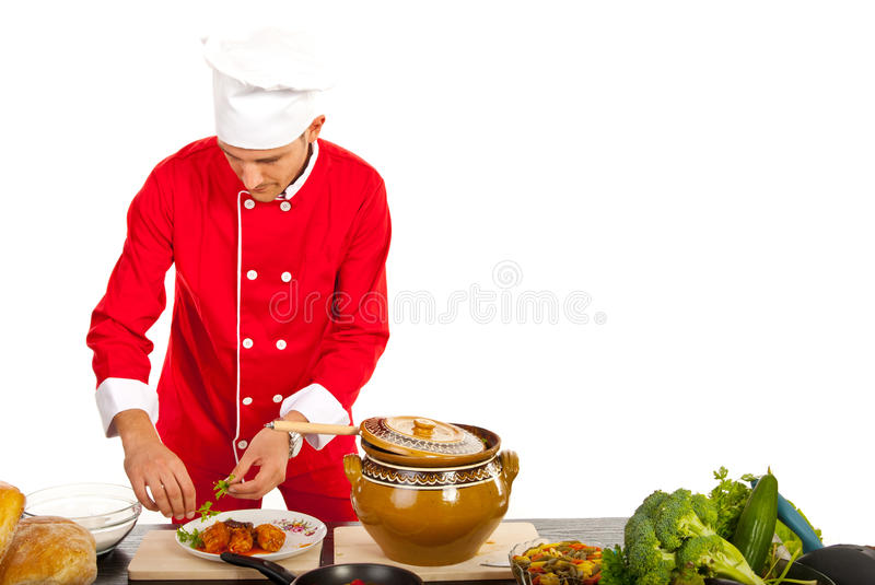 Chef garnish food on plate. Chef male garnish food on plate against white background royalty free stock photo