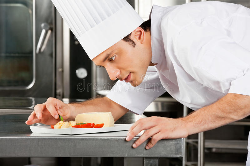 Chef Garnishing Dish. Young male chef garnishing dish in commercial kitchen royalty free stock photos