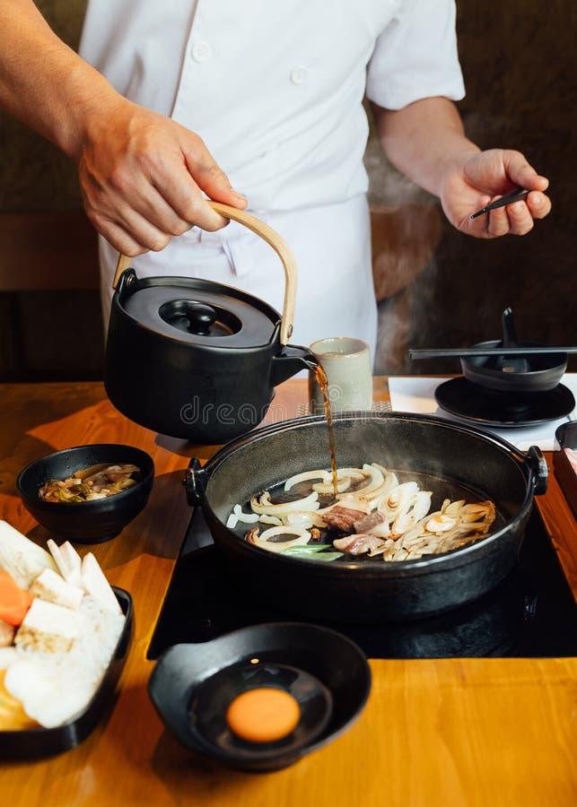 Chef gießt Shabu-Soßenmischung mit gebratenem Zwiebel-, Schalotte- und Rindfleischfett, bevor er Wagyu-Rindfleisch und Kurobuta-S lizenzfreies stockbild