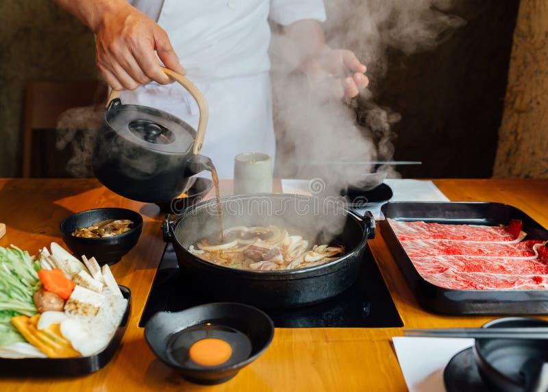 Chef gießt Sojasoße auf Aufruhr gebratenem Gemüse wie Zwiebel, Kohl, Schalotte und Tofu und mehr im heißen Topf mit Dampf stockbilder