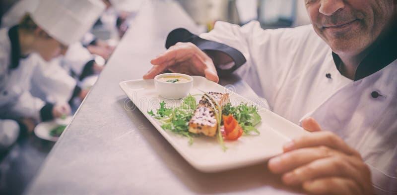 Chef glücklich mit fertigem Teller mit den Auszubildenden, die in der Küche arbeiten stockbild