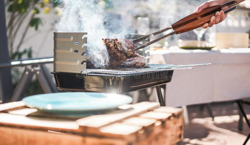 Chef grill t-bone steak at barbecue sunday lunch outdoor - Man cooking meat for a family bbq meal outside in backyard garden -. Summe lifestyle and food concept stock photography
