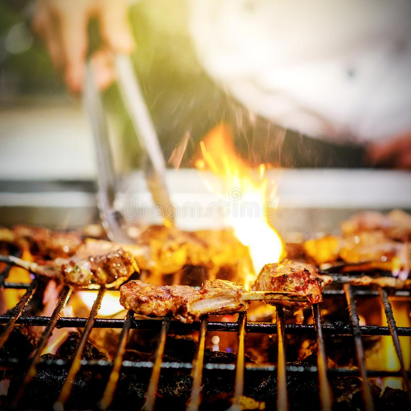 Chef grilling lamb ribs on hot flame royalty free stock photos