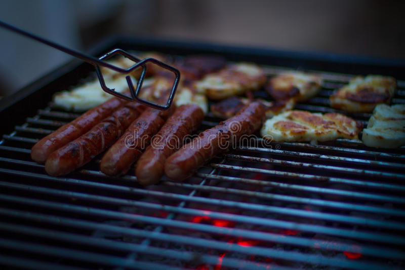 Chef grilling sausage on flame. BBQ with sausages and red meat on the grill - male hands holding a plate and taking the meat off the grill before it is too late royalty free stock photo