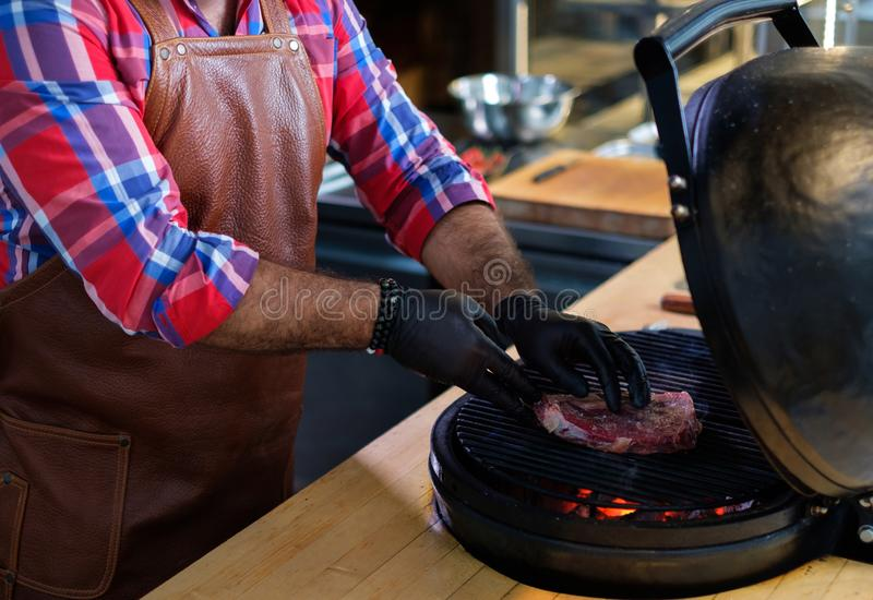 Chef grilling steak in a restaurant.  stock photography