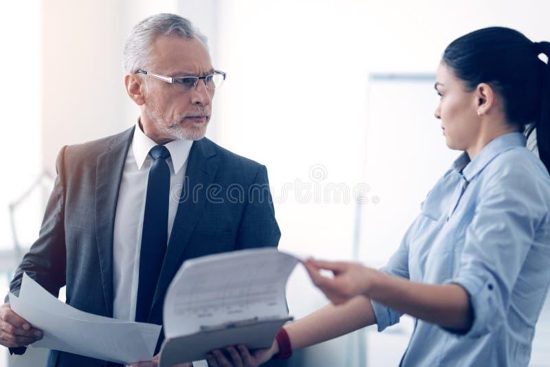 Chef grincheux et son employé de bureau féminin discutant au sujet des documents images stock