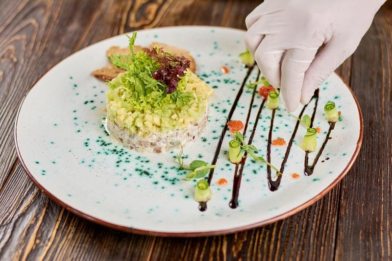 Chef hand decorating plate with salad. royalty free stock image