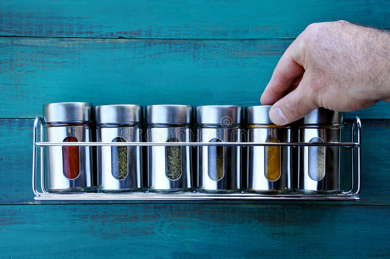 Chef hand returning spice into a spice rack royalty free stock photography